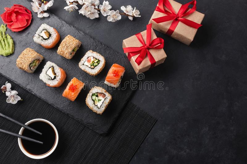 Set of sushi, maki rolls, gift boxes with branch of white flowers on stone table stock photography
