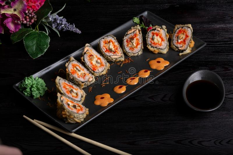 Set sushi rolls on a black rectangular plate on a dark background stock image