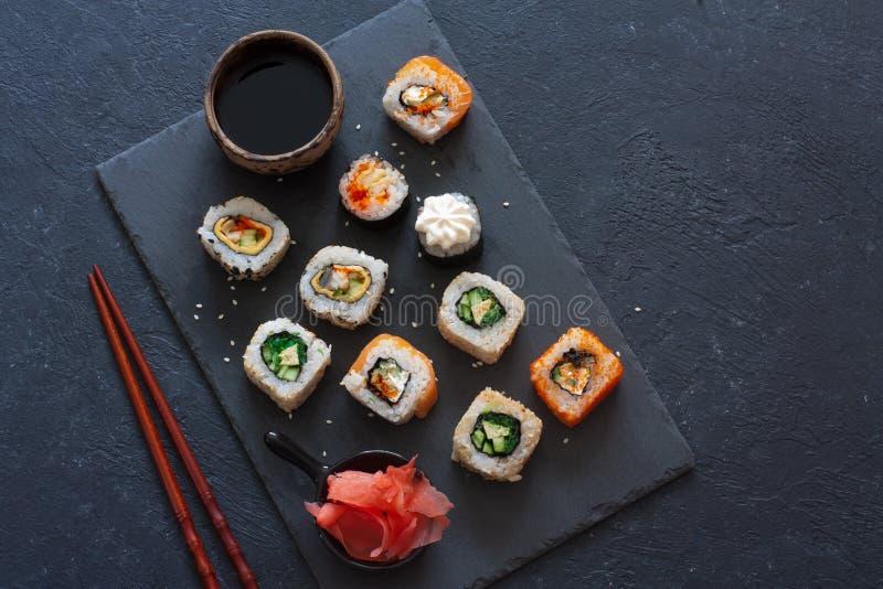 Set of sushi rolls served on stone slate royalty free stock photos