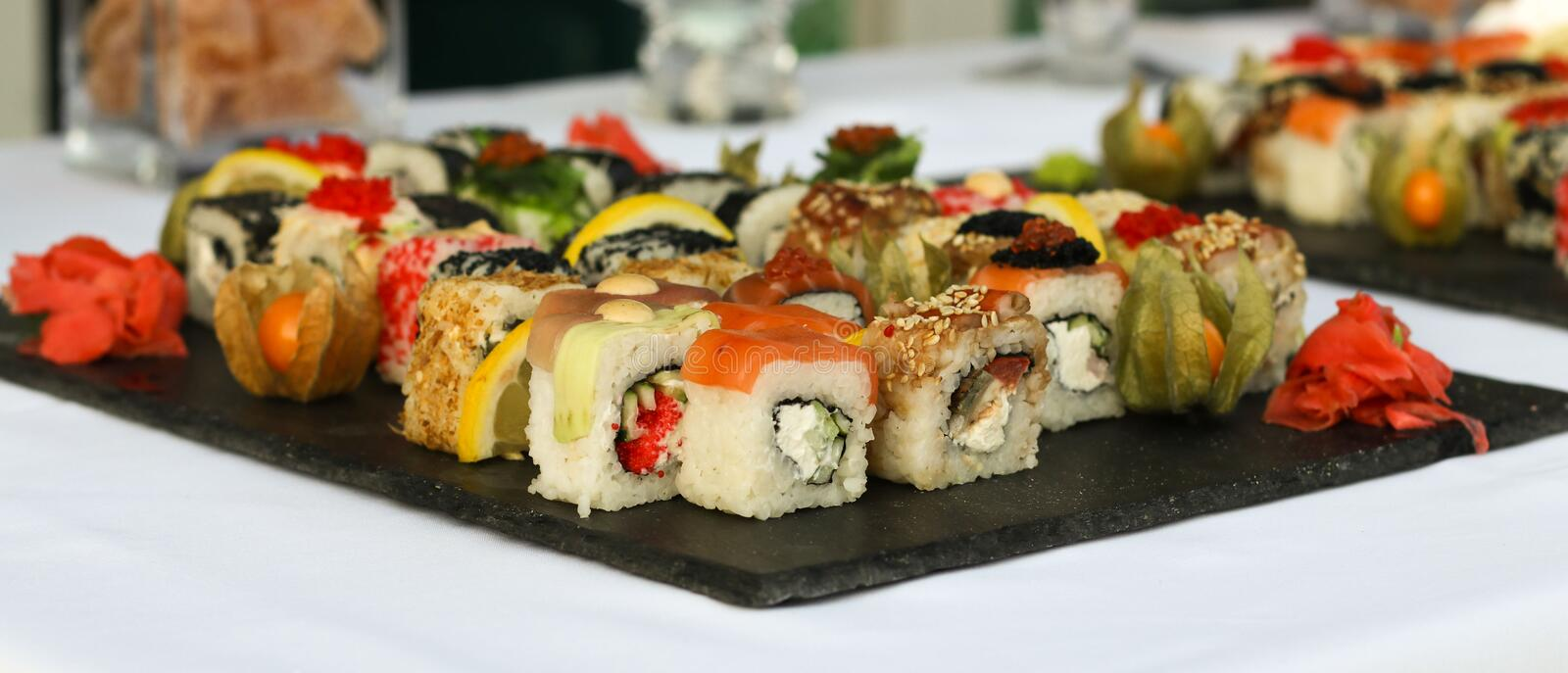 Set of sushi rolls with vasabi and ginger on a dark slate plate. royalty free stock images