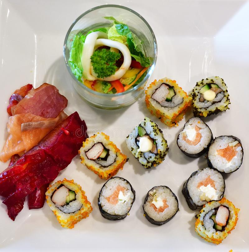 Set of sushi and salad in a glass on white plate royalty free stock photography