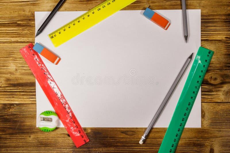 Set szkolne materia?y dostawy Pustego papieru prześcieradło, władcy, ołówki, gumki i ostrzarka na drewnianym biurku, Odg?rny wido zdjęcie stock