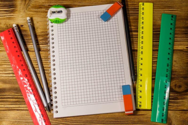 Set szkolne materia?y dostawy Pusty notepad, władcy, ołówki, gumki i ostrzarka na drewnianym biurku, Odg?rny widok zdjęcia royalty free