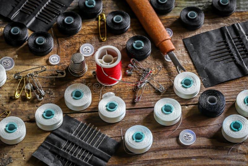 set szwalne nici i akcesoria na drewnianym tle obrazy stock