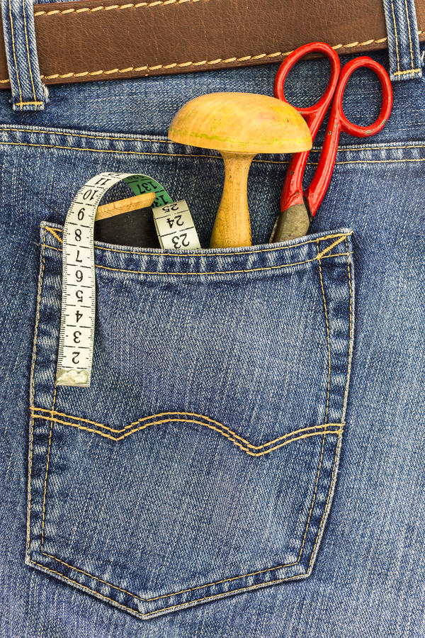Set of tailors tools in a back pocket of jeans. Set of tailors tools in a back pocket of a blue denim jeans royalty free stock images