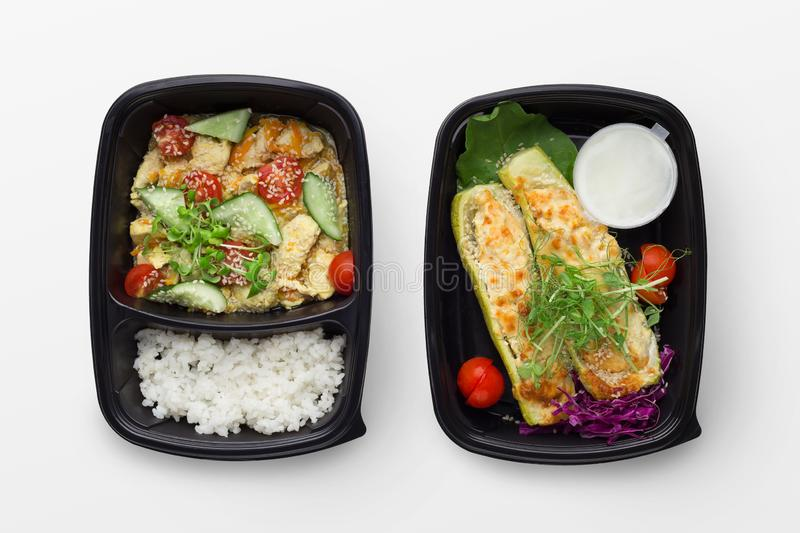 Set of take away difhes in black containers. Healthy eating food service. Rice with vegetables and baked zucchini in black delivery boxes, isolated on white royalty free stock image
