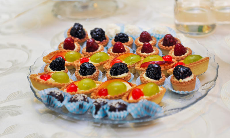 Set of tasty mini cakes with raspberries, blackberries, cranberries, blueberries and grapes on white table. Wedding decoration stock images