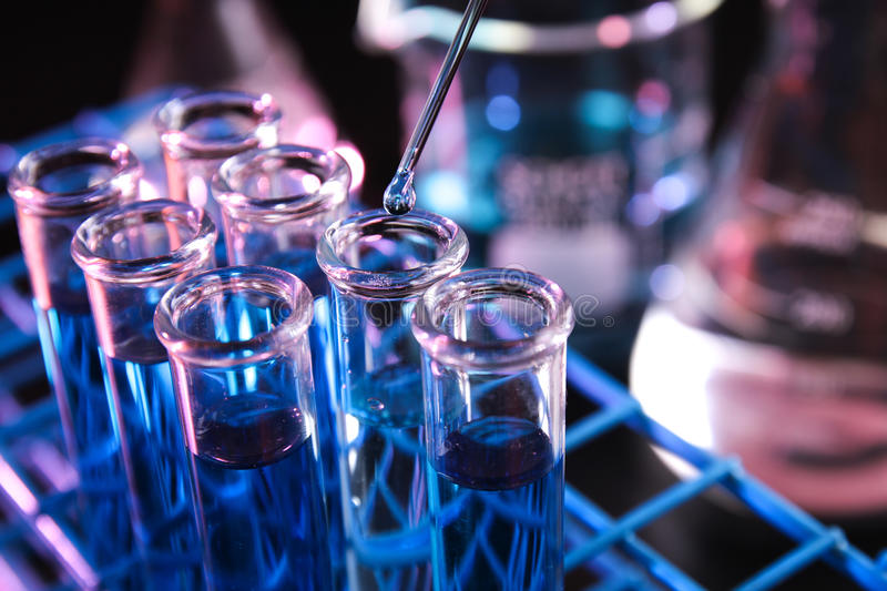 Set of test tubes filled with blue chemical in dark lab set up - Series 2 stock photography