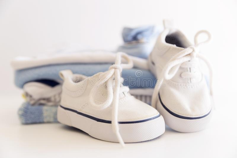Set of things for a newborn baby boy. Maternal concept. Baby clothes in pile and tiny baby shoes and hat stock photography
