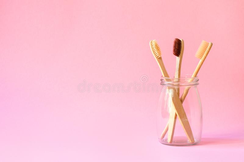 Set of three bamboo toothbrushes in glass bottle, family dental care, pink background, eco-friendly and plastic free lifestyle, de stock photography