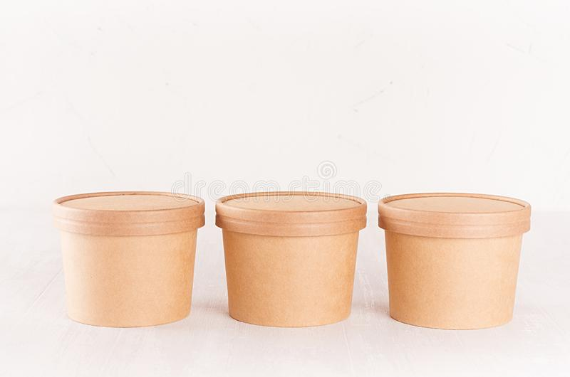 Set of three cardboard bowls with caps for fast food, soup or ice cream on white wood table, food branding identity mockup. royalty free stock photo
