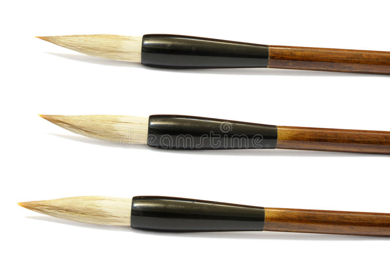 Set of three Chinese calligraphy brushes over a white background. Close-up of the tips of three Chinese calligraphy brushes resting on a white background royalty free stock photos