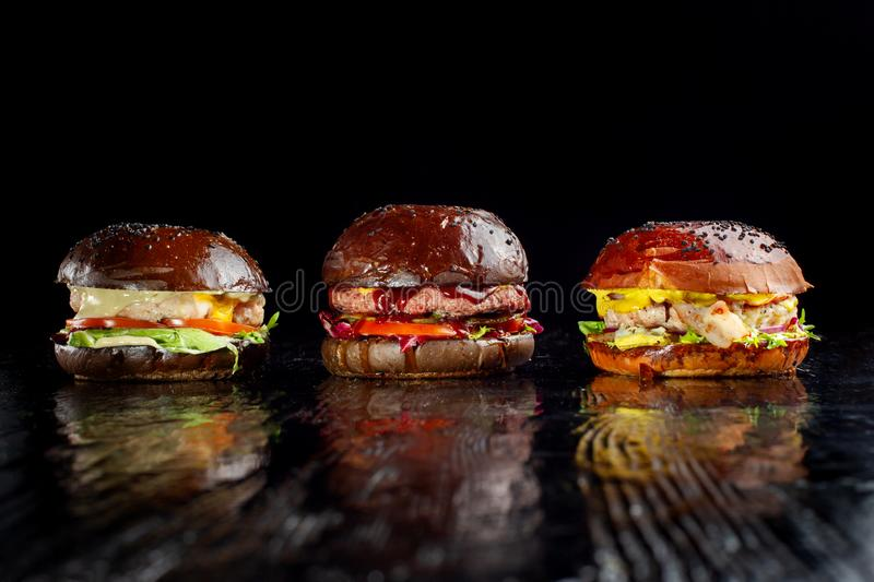 Set of three delicious burgers isolated on a dark background. The concept of fast food, delicious but unwholesome food. stock photos