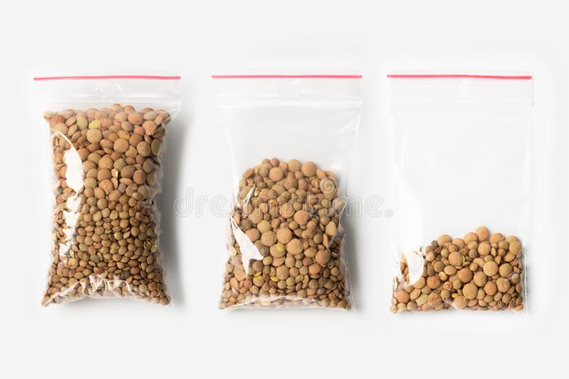 Set of three EMPTY, HALF AND FULL Plastic transparent zipper bag with lentils beans isolated on white. Vacuum package mockup with. Red clip. Concept stock photo