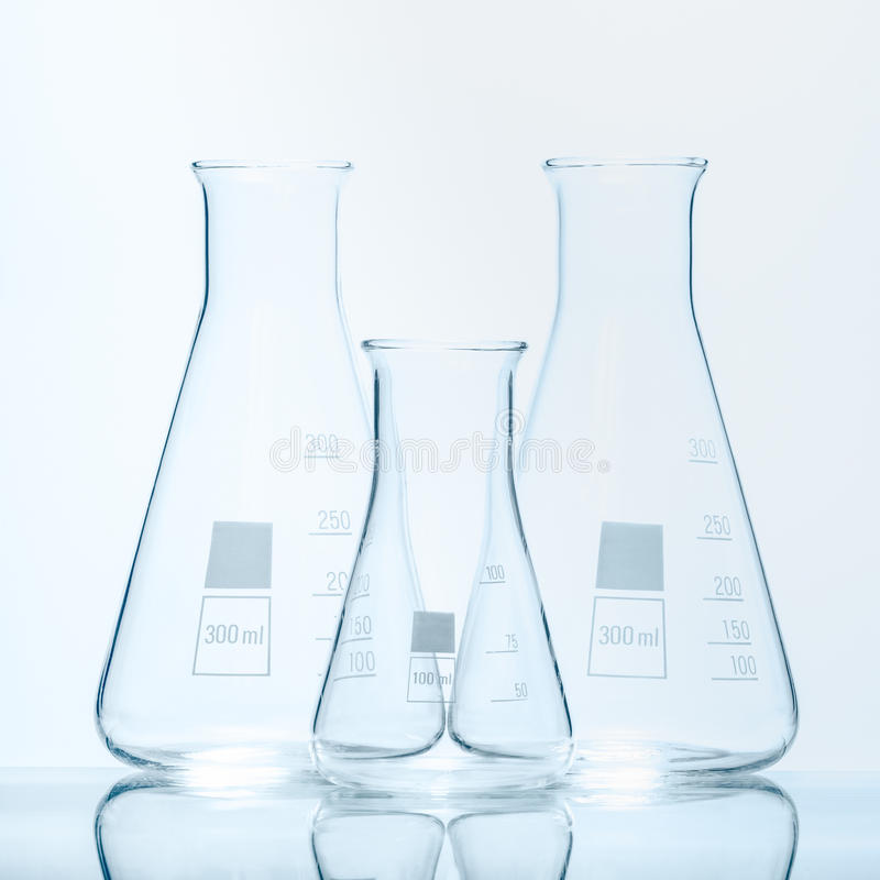 Set of three empty temperature resistant conical flasks for measurements. On white stock photo