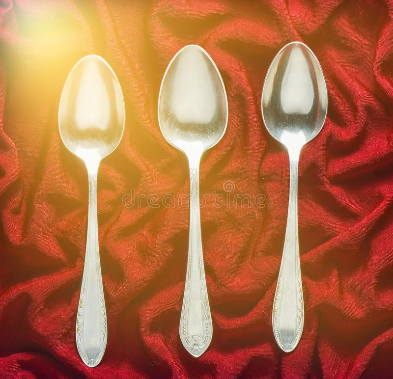 A set of three metal spoons on a red silk tablecloth. Top view stock photos