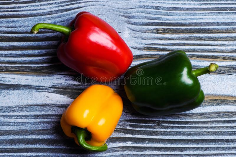Set of three peppers on wooden background. Yellow, red and green pepper royalty free stock photos
