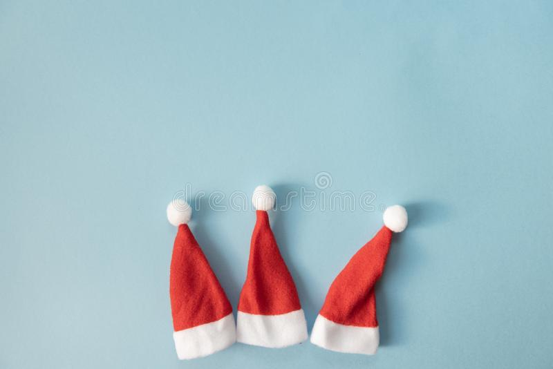 Set of three Santa Claus hats on a light blue background. Christmas or New Year concept. Minimalism. Copy Space royalty free stock photo