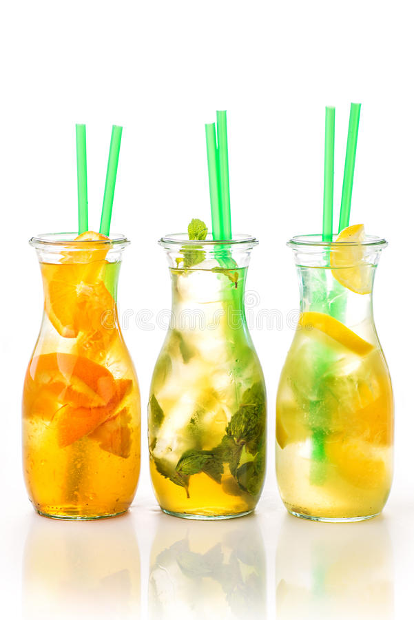 Set of three summer lemonade with ice and fruit like lemon, orange, lime and mint leaf, summer drink with soda isolated on white b royalty free stock images