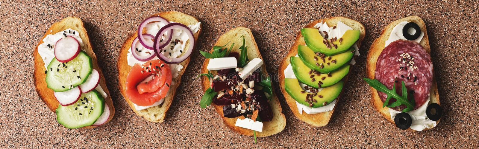 Set with toast bread and different toppings, salmon, smoked sausage, vegetables and feta cheese on a brown stone background. Top. View stock image