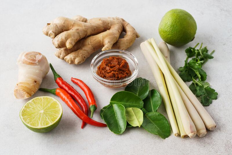 Set of Tom Yum soup basic ingredients for cooking. Set of Tom Yum soup basic ingredients - Tom Yum paste, lemon grass, chilli peppers, galanga root, ginger and stock photo