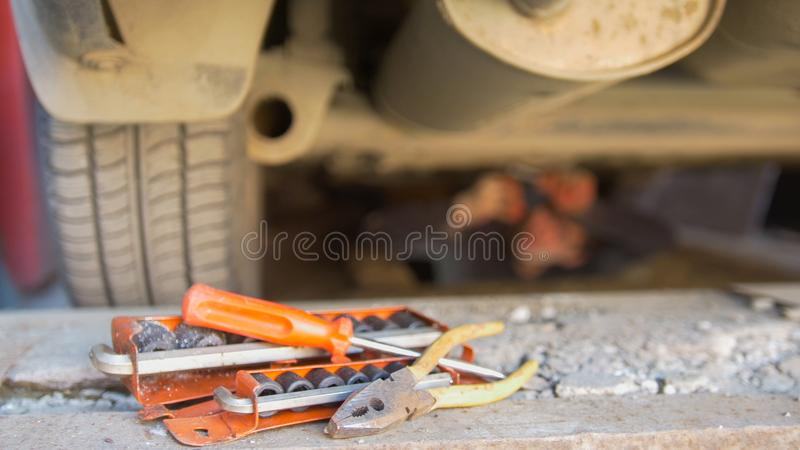 Set of tools in front of mechanic underneath a car screwing details on under tray stock image