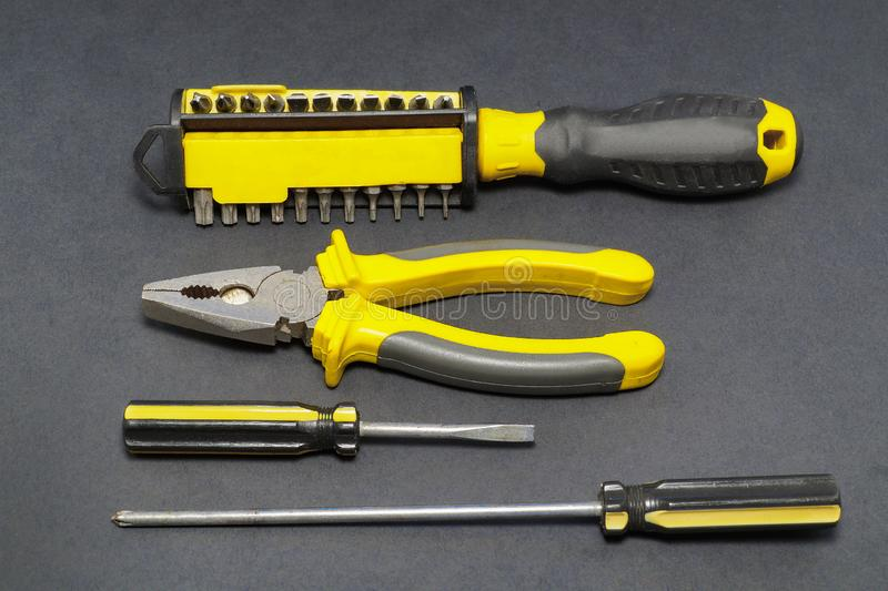 A set of tools on a gray background pliers, screwdriver. royalty free stock images