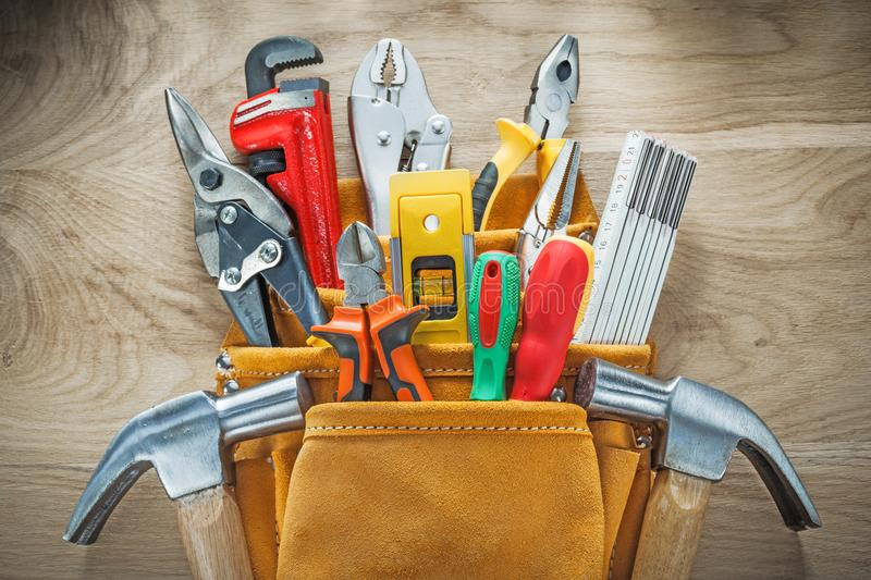 Set of tools in leather construction belt on wooden board royalty free stock photos