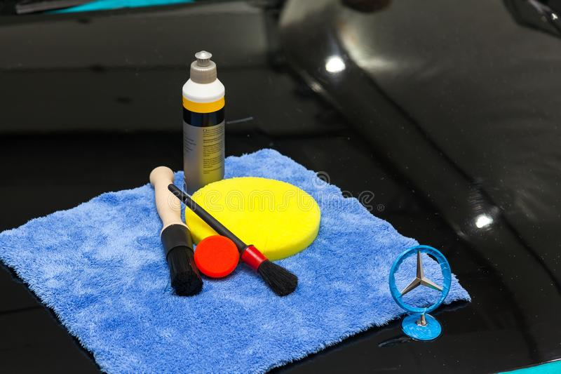 A set of tools for polishing and washing a car consisting of blue microfiber, a large yellow circle and a small red brush and a stock images