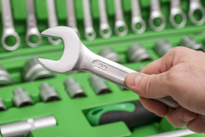 A set of tools for repair in car service - mechanic`s hands, close up. Auto mechanic with working tools for repair and diagnostic royalty free stock image
