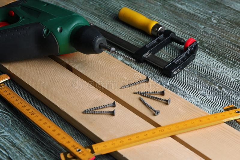 Set of tools and wooden boards on table in carpenter`s workshop royalty free stock image