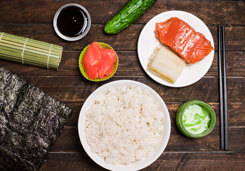 Set of traditional japanese food on a dark background. Sushi rolls, nigiri, raw salmon, rice, pickled ginger. Asian food frame. M. Aking sushi at home royalty free stock image