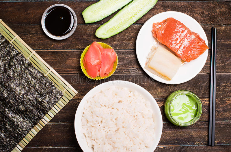 Set of traditional japanese food on a dark background. Sushi rolls, nigiri, raw salmon, rice, pickled ginger. Asian food frame. M. Aking sushi at home royalty free stock photo