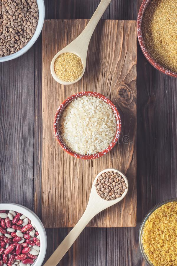 Set Traditional organic vegan ingredient Super Food in Middle East and Asian cooking cereals. Red lentil lens culinaris rice wheat beans bulgur culinary spoons stock photo