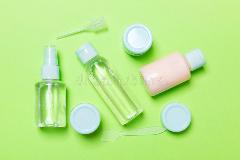 Set of travel size cosmetic bottles on green background. Flat lay of cream jars. Top view of bodycare style concept.  stock photography