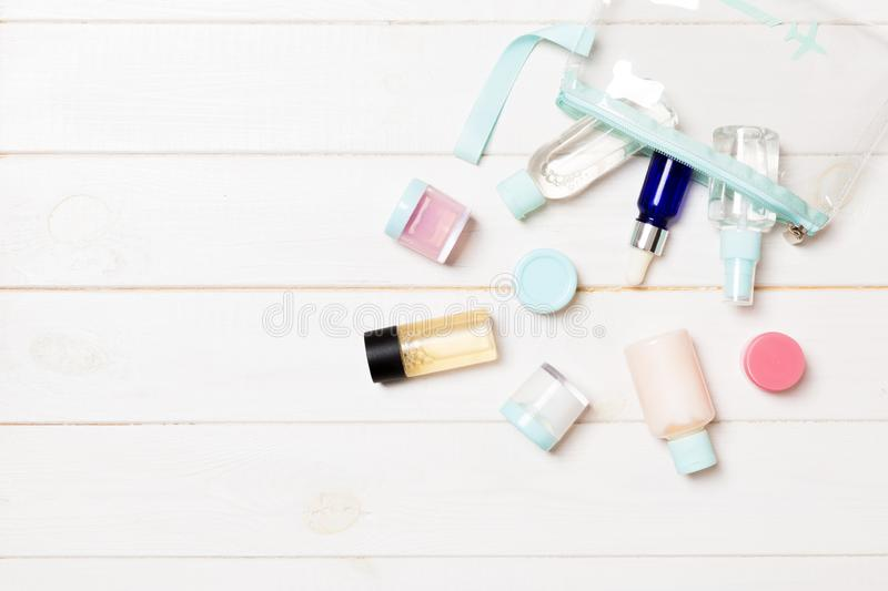 Set of travel size cosmetic bottles on white wooden background. Flat lay of cream jars. Top view of bodycare style concept.  royalty free stock photo