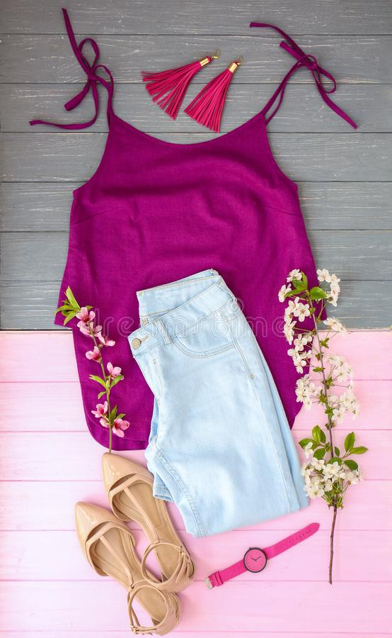 Set of trendy female clothes, accessories and blossoming branches on wooden background, flat lay stock photography