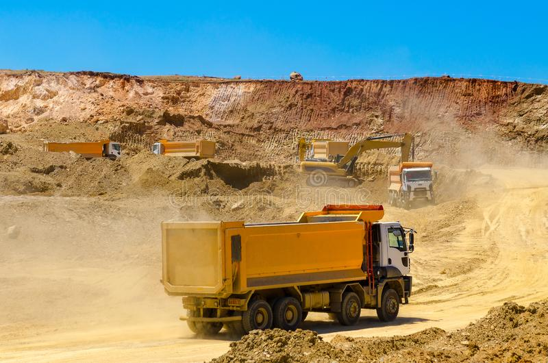 Trucks and the excavator work in career at mining stock photo