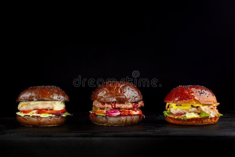 Set trzy wyśmienicie hamburgeru odizolowywającego na ciemnym tle Pojęcia fast food, wyśmienicie ale unwholesome jedzenie obraz royalty free