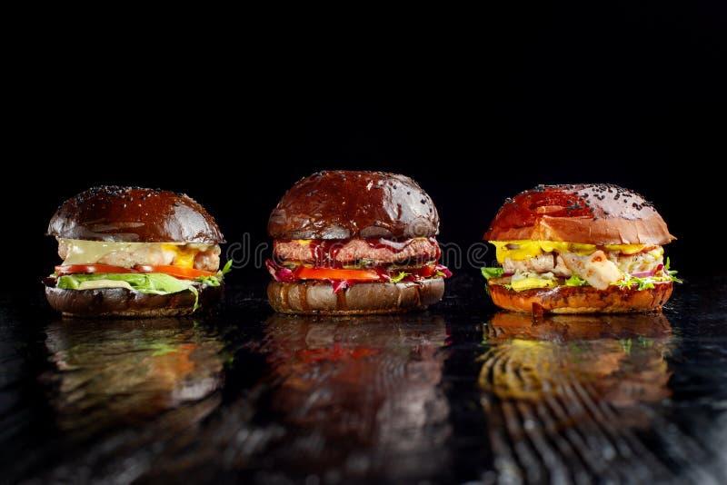 Set trzy wyśmienicie hamburgeru odizolowywającego na ciemnym tle Pojęcia fast food, wyśmienicie ale unwholesome jedzenie zdjęcia stock