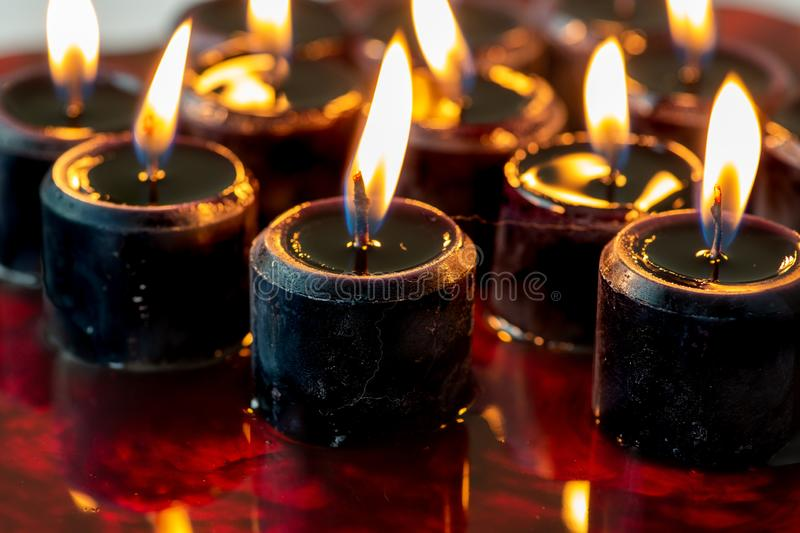 A set of twelve black candles lit sitting on a large pool of blood. Perfect scary background for Halloween royalty free stock photo