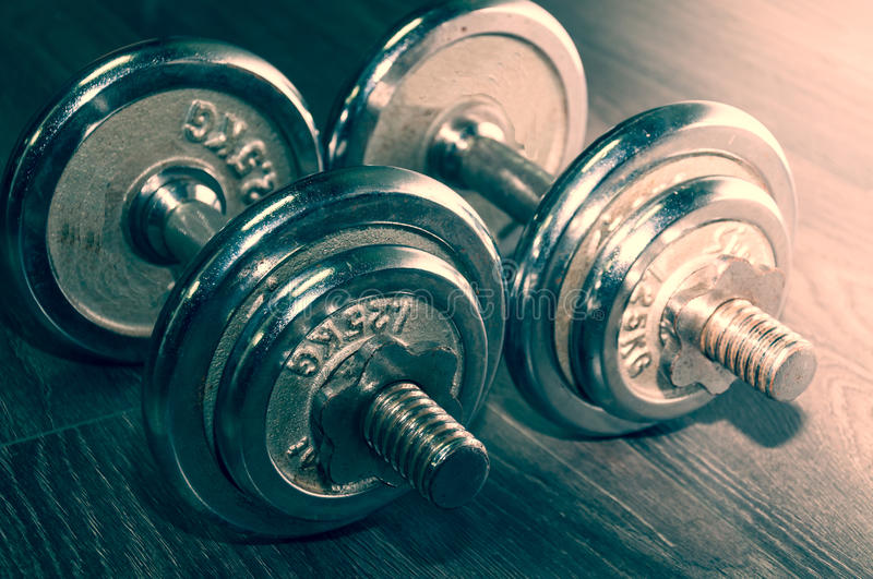 Set of two iron weights on the gym floor.  stock image