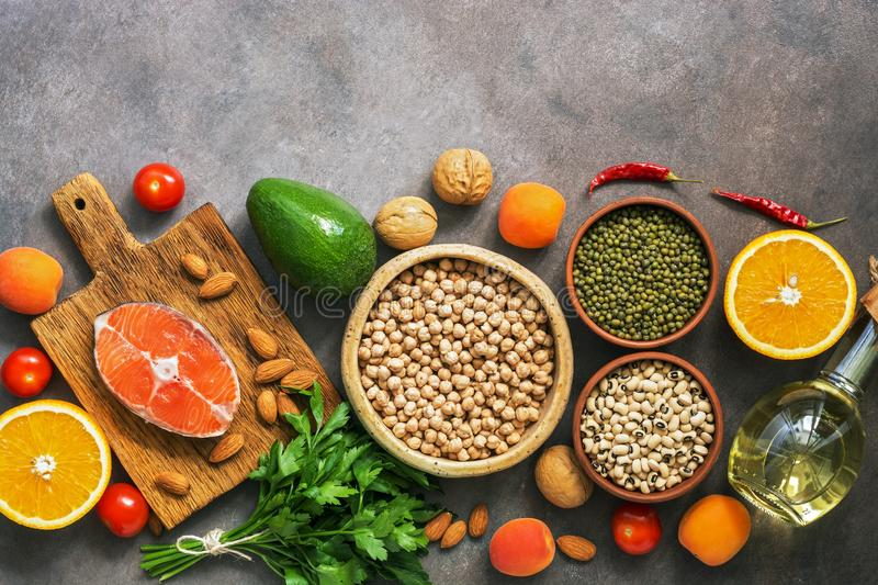 Set uncooked healthy balanced food, salmon,legumes, fruits, vegetables, olive oil and nuts, dark rustic background. Overhead view royalty free stock image
