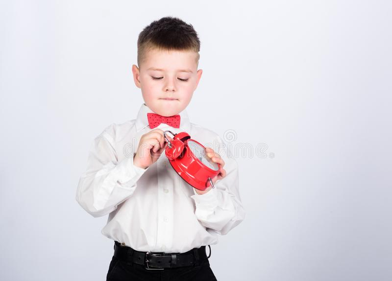 Set up alarm clock. Child little boy hold red clock. It is time. Morning routine. Schoolboy with alarm clock. Kid. Adorable boy white shirt red bow tie. Develop stock photos