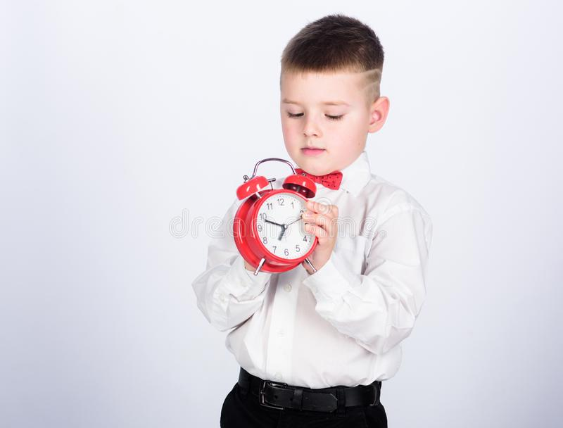 Set up alarm clock. Child little boy hold red clock. It is time. Schedule and timing. Morning routine. Schoolboy with. Alarm clock. Kid adorable boy white shirt royalty free stock photography