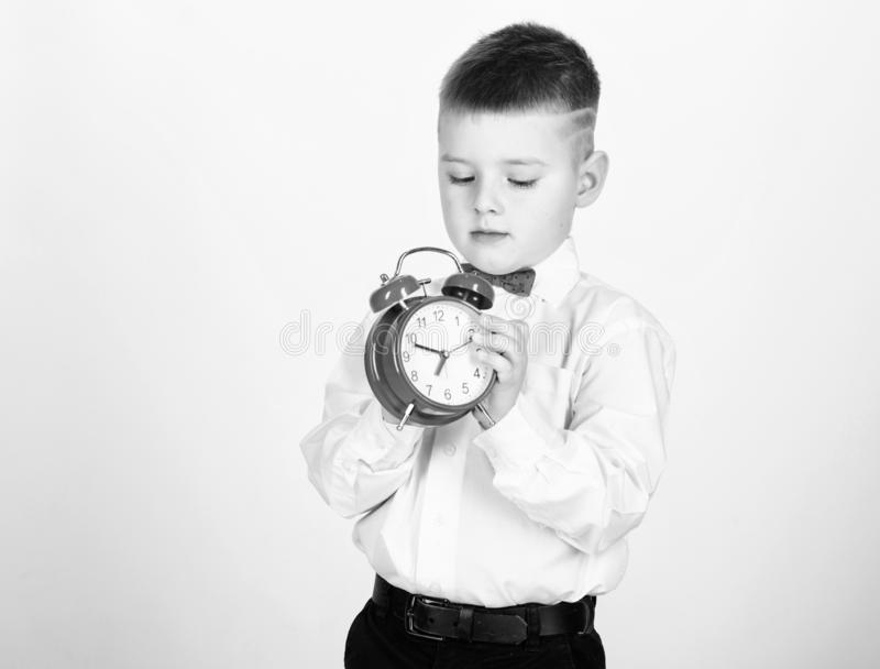 Set up alarm clock. Child little boy hold red clock. It is time. Schedule and timing. Morning routine. Schoolboy with. Alarm clock. Kid adorable boy white shirt royalty free stock photos
