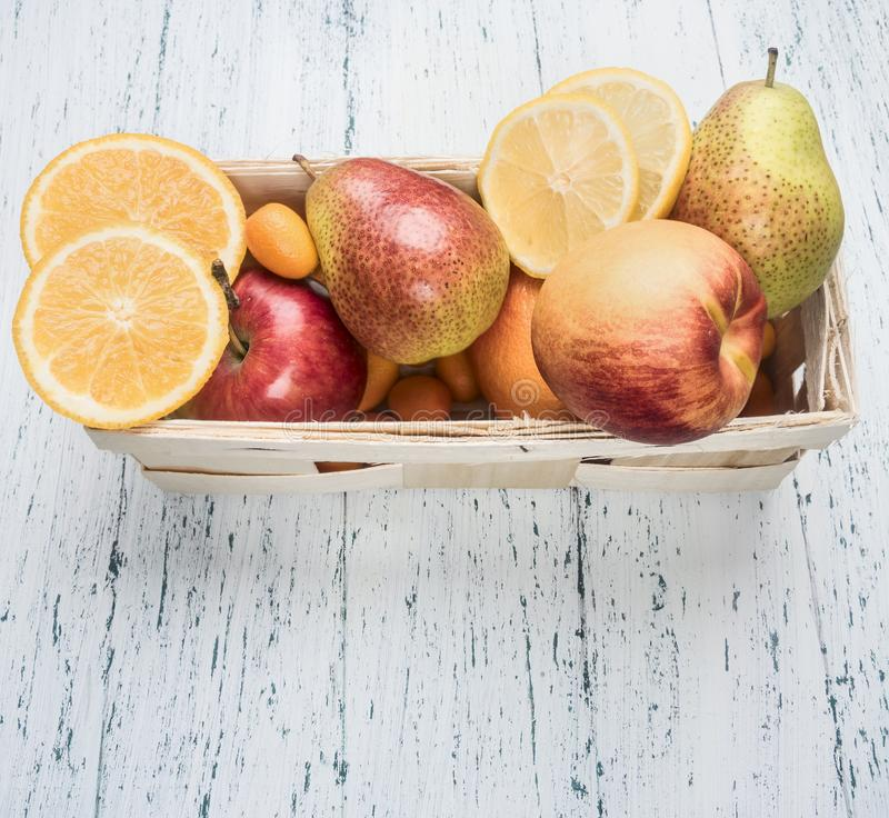 Set of useful fruits, pears, oranges, kumquat, apples, in a white basket on white rustic wooden background, place for text royalty free stock photo