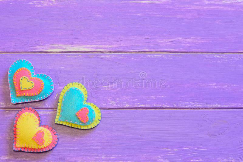 Set of Valentines Day felt hearts. Pretty felt heart decor on a wooden background with empty space for text. Valentines ornaments. Valentine`s Day heart crafts royalty free stock photography