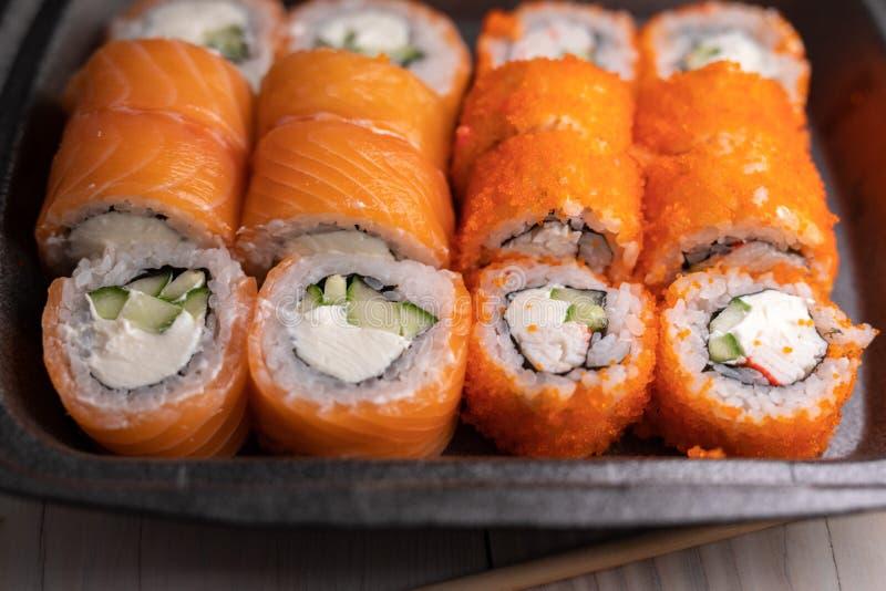 Set van geassorteerde sushi in een zwarte doos op houten tafel california en philadelphia rolls royalty-vrije stock foto