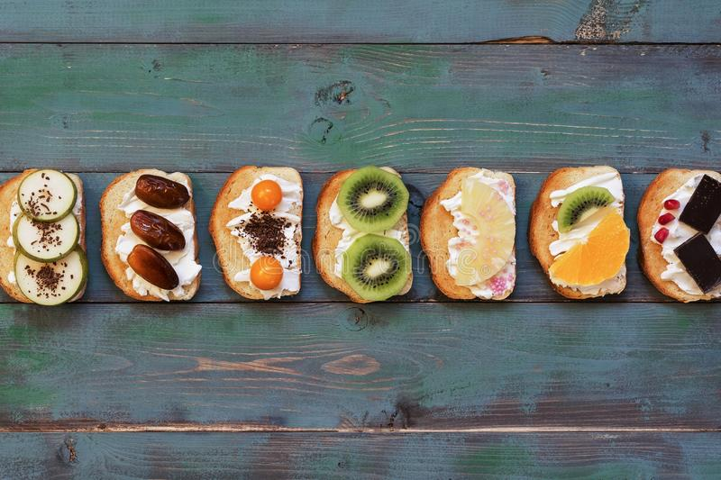 Set of a variety of sweet sandwiches on a green wooden plank background. Top view, place for text stock photos